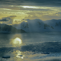 Sunset over Antarctic Peninsula near Adelaide Island & Danco Coast.