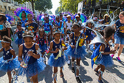 Young performers make their way down Ladbroke Grove as day one, Children's Day, of the Notting Hill Carnival gets underway in London. London, August 25 2019.