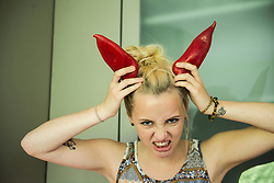 Portrait of a beautiful young woman making horns with two paprika on her head, Munich, Bavaria, Germany