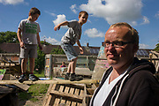 Father and boys in risk averse playground called The Land on Plas Madoc Estate, Ruabon, Wrexham, Wales. Young people are encouraged to push their personal limits in a way that parents are nowadays scared to allow. But here in this council play park, children are encouraged to experiment with risk aversion, to enjoy a wilder form of play and interaction with others - the opposite of online relations and over safe childhoods. From the chapter entitled 'Playing with Fire' from the book 'Risk Wise: Nine Everyday Adventures' by Polly Morland (Allianz, The School of Life, Profile Books, 2015).