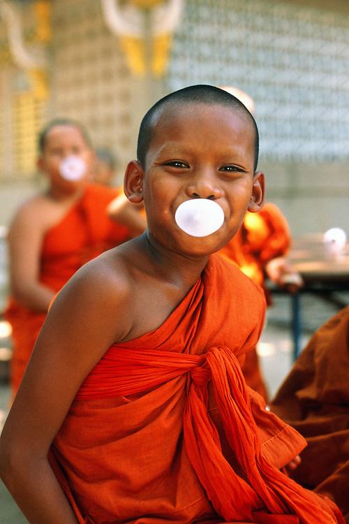 Novice buddhist monks blow bubble-gum in the monastery in Kanchanaburi