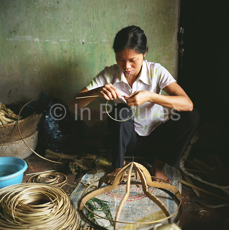 Woman preparing bamboo for making a traditonal palm leaf hat in Uoc Le village, Ha Tay province, Vietnam. With Vietnam's growing population making less land available for farmers to work, families unable to sustain themselves are turning to the creation of various products in rural areas.  These 'craft' villages specialise in a single product or activity, anything from palm leaf hats to incense sticks, or from noodle making to snake-catching. Some of these 'craft' villages date back hundreds of years, whilst others are a more recent response to enable rural farmers to earn much needed extra income.