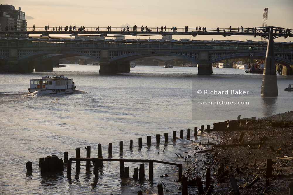 """A pleasure boat passes old riverside wharf timbers and the bank of the river Thames, before continuing under pedestrians on the Millennium Bridge, on 30th October 2017, at Queenhithe in the City of London, England. Queenhithe is also the name of the ancient, but now disused, dock which derives from the """"Queen's Dock"""", or """"Queen's Quay"""", which was probably a Roman dock (or small harbour). The dock existed during the period when the Wessex king, Alfred the Great, re-established the City of London, circa 886 AD."""