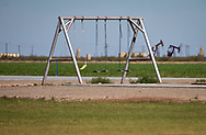 Swing set in Verhalen, Texas in the Permian Basin across from oil and gas industry sites.