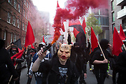 Anarchists gather as a black bloc for the Fuck Parade to party and protest at the class and wealth divide between rich and poor and the gentrification of London, the demonstration was organised by anarchist group Class War on May 1st 2016 in London, United Kingdom. The parade is now part of the May Day activism calendar as dissatisfaction about the establishment, the police and the inadequacy of the press is highlighted. Protester wearing a pig face head emblazoned with the letters ACAB (meaning All Coppers Are Bastards) amonst coloured smoke from a smoke bomb. (photo by Mike Kemp/In Pictures via Getty Images)