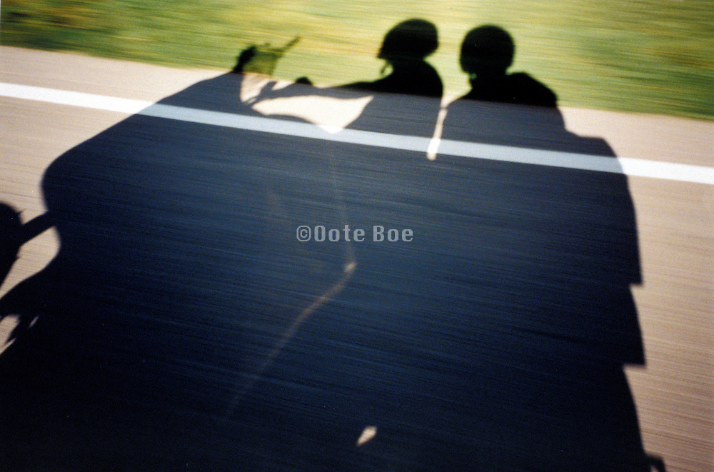 shadow of a moving motorcycle with 2 people on board