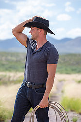 hot rugged cowboy holding a lasso on a ranch with mountain views