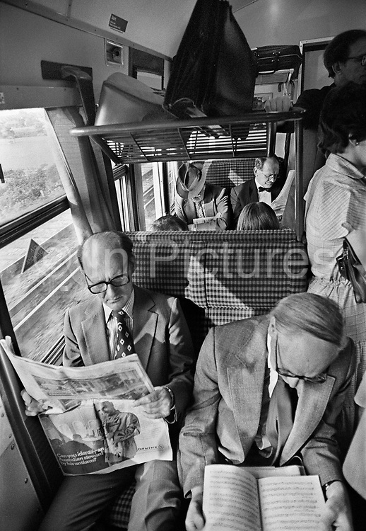 """Crowded Guilford train heading for Waterloo, 8.00am. Most travellers on this Southern Region train would be middle class season ticket holders.<br /> British rail was the sole transport option for many rural areas. However, after """"The Beeching Report"""" many connections to villages were cut even before the wide spread of cars (for example in 1960s and 1970s) and public transport was nothing or based on coaches. Coming and Going is a project commissioned by the Museum of London for photographer Barry Lewis in 1976 to document the transport system as it is used by passengers and commuters using public transport by trains, tubes and buses in London, UK."""