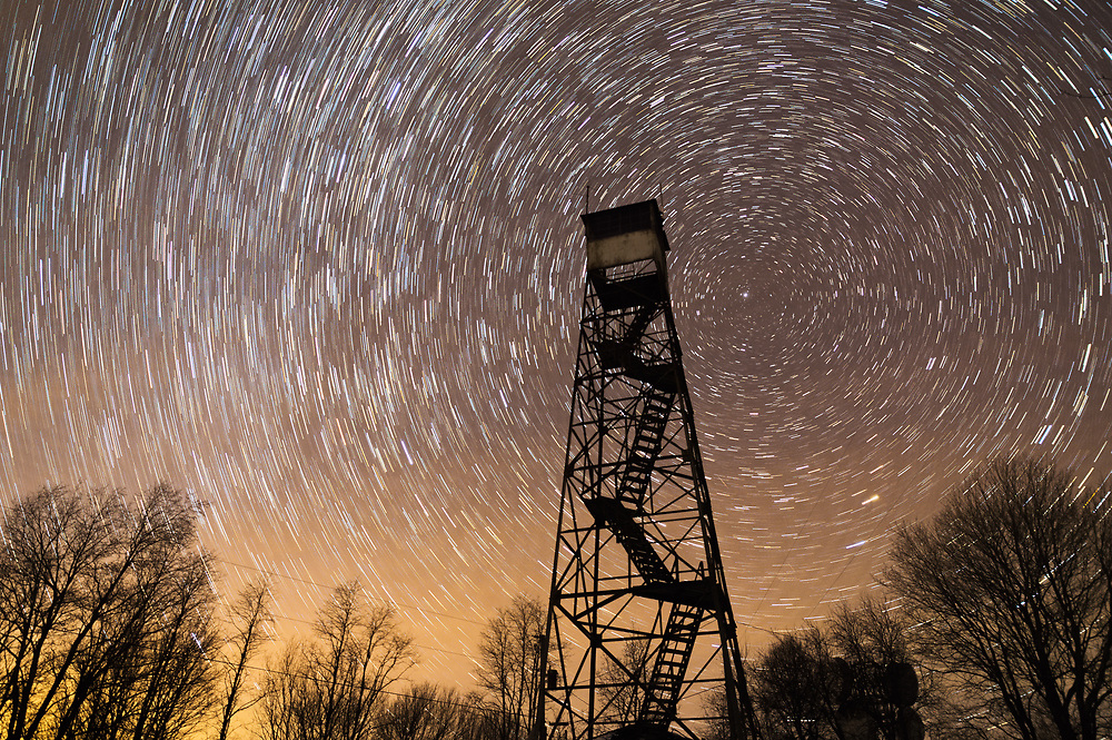 An abandoned fire tower stands silhouetted against the dark night sky as stars circle around the north star.