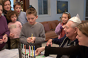 Child lights the candles in a Chanukkah Menorah with the whole family watching