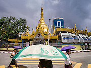 12 JUNE 2013 - YANGON, MYANMAR:  People walk past Sule Pagoda in Yangon, Myanmar. Sule Pagoda is one of the city's oldest and most revered Buddhist temples and landmark for central Yangon.        PHOTO BY JACK KURTZ