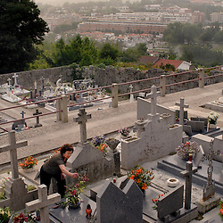 Pousada de Santa Marinha, Portugal -A woman places flowers on and cleans her father's grave at the cemetery adjacent to  the Pousada do Santa Marinha, a former convent nestled above the hills outside of Guimaraes, the first capitol of Portugal...Photo by Susana Raab
