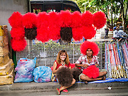 19 MAY 2013 - BANGKOK, THAILAND:   Red Shirt vendors comb out red fright wigs to sell to Red Shirts during a rally honoring Red Shirts killed by the Thai army during the Red Shirt protests in 2010. More than 85 people, most of them civilians, were killed during the Thai army crackdown against the Red Shirt protesters in April and May 2010. The Red Shirts were protesting against the government of Abhisit Vejjajiva, a member of the opposition who became Prime Minister after Thai courts ruled the Red Shirt supported government was unconstitutional. The protests rocked Bangkok from March 2010 until May 19, 2010 when Thai troops swept through the protest areas arresting hundreds.   PHOTO BY JACK KURTZ