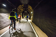 Cyclists enjoy riding through the restored Devonshire Tunnel which is part of the Two Tunnels Greenway near Bath, Somerset, England, United Kingdom on 6th April 2013.  The tunnel is 407 meters long and has been restored so it is accessible by foot, cycle or wheelchair and well light throughout.  The tunnel was previously part of a main railway line, the walls are blackened with a thick crust of soot from engine exhaust, while a strip in the roof is blasted clean by that same exhaust.  The tunnel is stone-lined throughout and on a curved and falling 1:50 gradient.  The tunnel is part of a 13-mile route and was restored by Sustrans in partnership with Bath and North East Somerset Council.  The opening of the route was attended by hundreds of cyclists and pedestrians to celebrate the new access to beautiful Somerset country-side.
