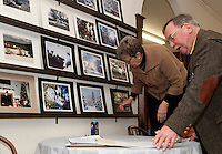 Jeanne Lowrey and Robert Greemore display a series of winter season photographs to be judged and selected for inclusion into a Wicwas Grange 2013 calendar.  (Karen Bobotas/for the Laconia Daily Sun)