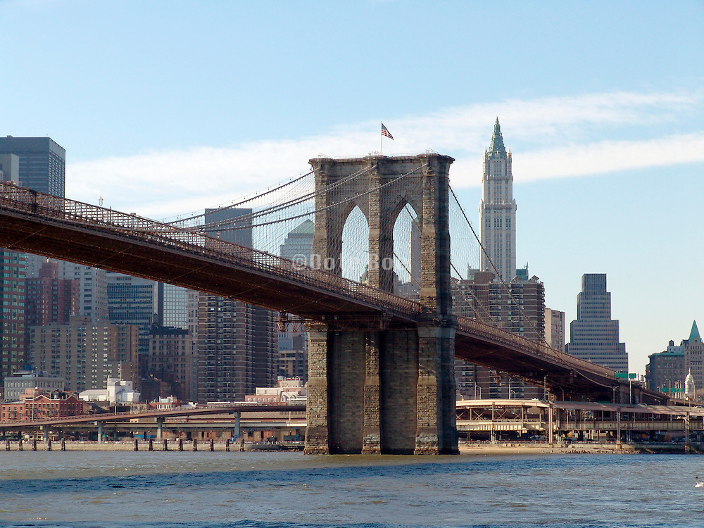 View of the Brooklyn Bridge with the Woolworth building in the background.