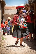 Quechua woman in traditional dress, carries child, Chinchero Town Sunday Market, Cusco region, Peru, South America