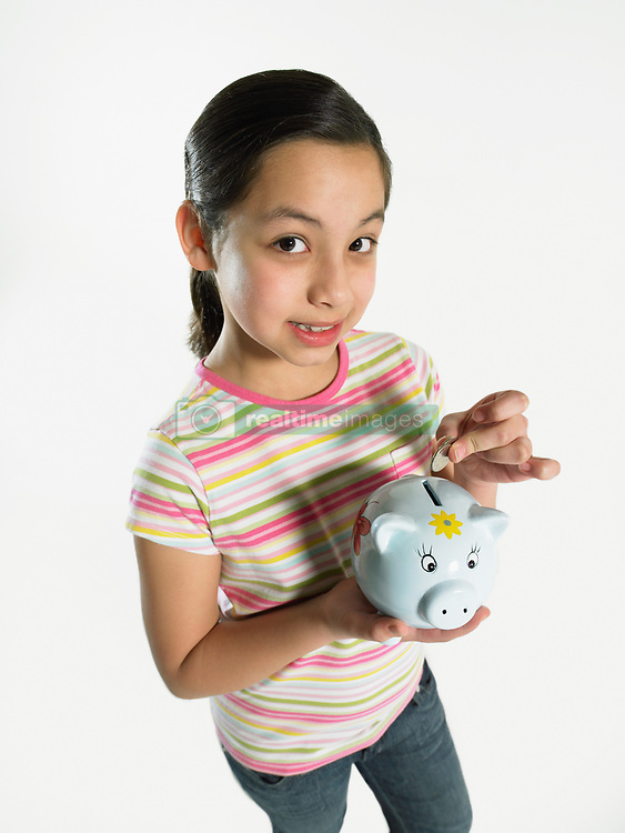 Dec. 14, 2012 - Girl putting money in piggy bank (Credit Image: © Image Source/ZUMAPRESS.com)