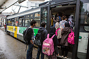 Passengers wait and queue to board an electric tram bus in Ghent, Belgium.