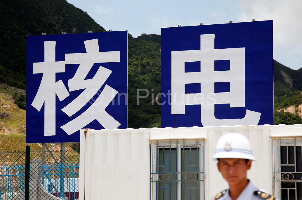 """A guard walks under billboards with the Chinese character meaning """"nuclear power"""" at the Taishan Nuclear Power Plant project in Taishan, Guangdong Province, China, on July 29, 2010. Despite concerns toward the safety of nuclear power as demonstrated by Japan's Fukashima disaster, China is forging ahead with its plans of rapidly expanding its nuclear power generation capacity."""