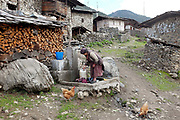 A Brokpa woman washes clothes and collects water for household use at the standpipe in the remote and roadless village of Merak, Eastern Bhutan. The Brokpa, the semi-nomads of the villages of Merak and Sakteng are said to have migrated to Bhutan a few centuries ago from the Tshona region of Southern Tibet. Thriving on rearing yaks and sheep, the Brokpas have maintained many of their unique traditions and customs. In summer they move to the pastures with their yaks and sheep and in winter they return to live in their houses, normally built of stones with small ventilation to protect from the piercing cold weather.