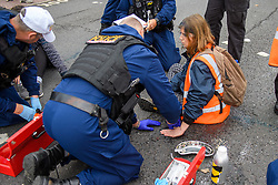 """© Licensed to London News Pictures. 27/10/2021. London, UK. A police officer removes a glued-on protester from climate campaign 'Insulate Britain', an offshoot of Extinction Rebellion (XR), as they block traffic on the A40 Western Avenue in Acton. Following a national injunction covering England's highways, Insulate Britain declared the M25 """"a site of nonviolent civil resistance"""" vowing to return to the motorway network to continue their protest action. Photo credit: Peter Manning/LNP"""