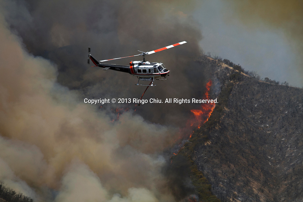 A helicopter prepares to make a water drop onto a wildfire, Friday May 31, 2013, near Castiac, California. Fourteen aircraft and more than 550 firefighter were deployed in a ground and air campaign against a brush fire that has blackened about 1,500 acres in sparsely populated San Francisquito Canyon in the Angeles National Forest northeast of Santa Clarita. The Powerhouse Fire, which broke out Thursday afternoon, was about 15 percent contained. The estimated date of full containment is Wednesday, June 5. (Photo by Ringo Chiu/PHOTOFORMULA.com)