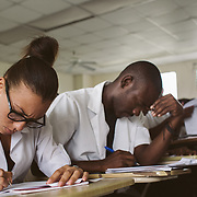 INDIVIDUAL(S) PHOTOGRAPHED: Marie Danielle Bazile (left) and unknown (right). LOCATION: University of the Artistide Foundation (UNIFA), Tabarre Commune, Port-au-Prince, Haïti. CAPTION: Marie Danielle Bazile concentrates on completing her questionnaire.