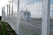 A truck passes on the motorway above the camp for refugees known as 'The Jungle'. New security fencing has been erected to stop refugees trying to board trucks bound for United Kingdom.