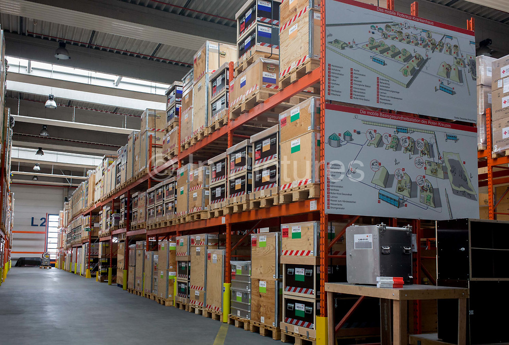 Emergency supplies warehouse, Deutsches Rotes Kreuz (DRK - German Red Cross) at their logistics centre at Berlin-Schönefeld airport. Ready for immediate loading into disaster zones, the equipment is stored near to where freight aircraft can fly anywhere in the world. The International Red Cross and Red Crescent Movement, with its 187 National Societies, is the world's largest humanitarian network. The German Red Cross is part of this universal community, which started 150 years ago to deliver comprehensive aid to people affected by conflict, disaster, sanitary emergencies, or social hardship, guided solely by their needs. Around four million volunteers and members support the Red Cross in Germany alone.
