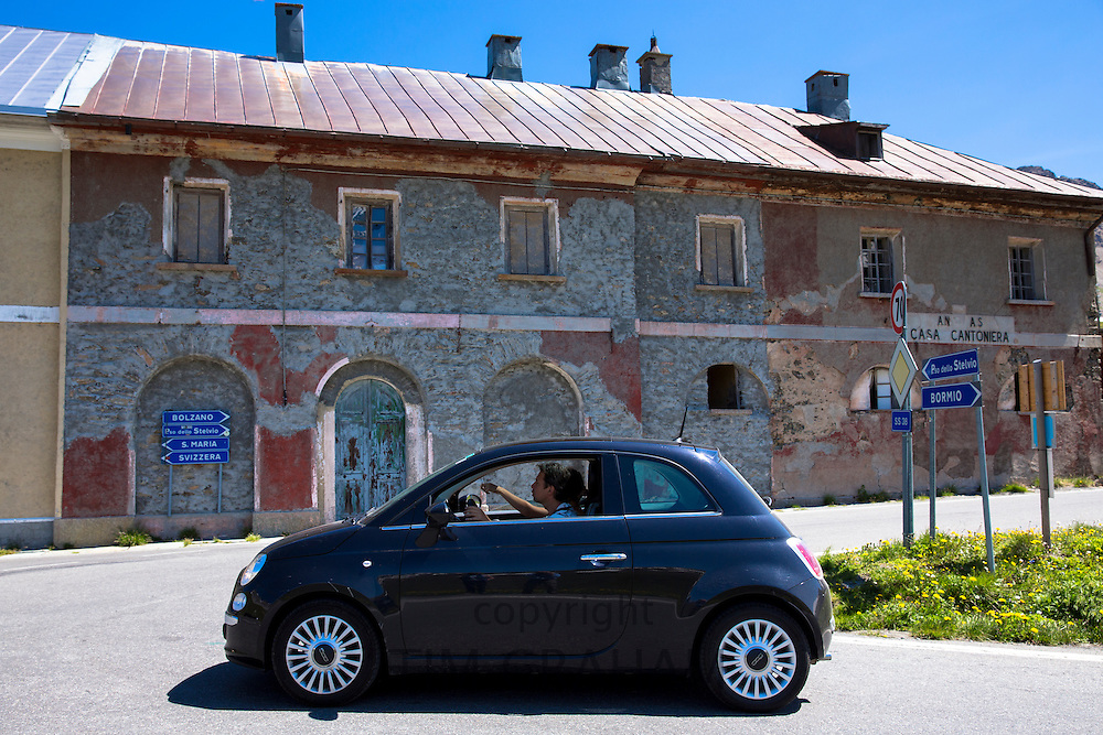 Couple in Fiat 500 passe signpost on The Stelvio Pass, Passo dello Stelvio, Stilfser Joch, in Italy head for Switzerland