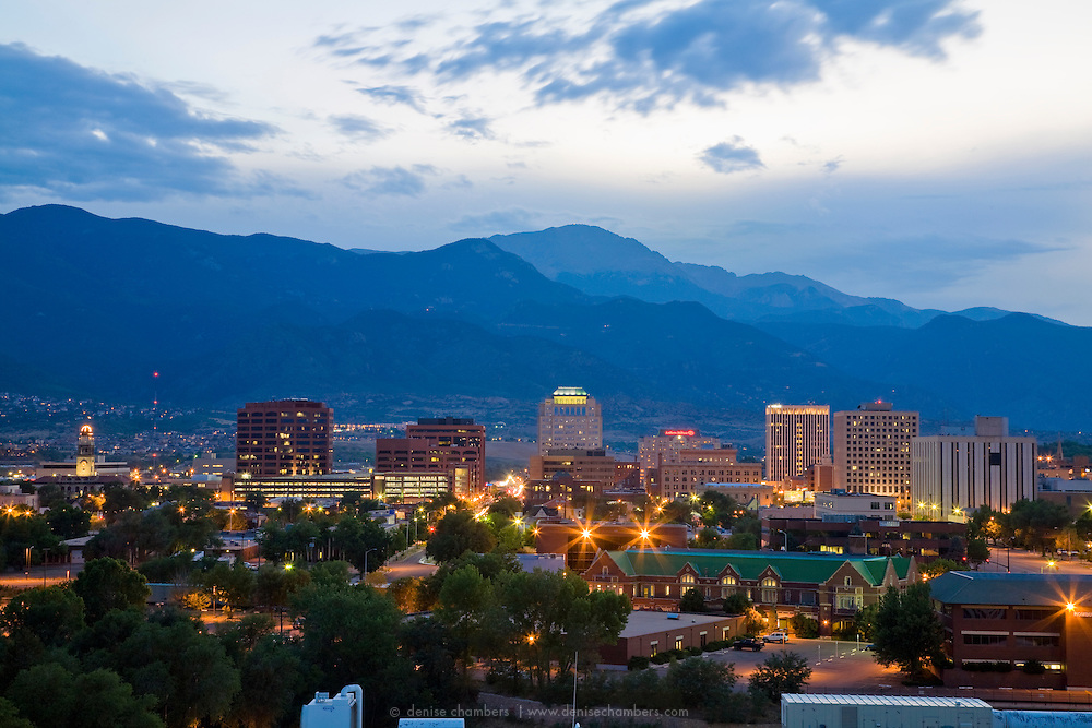 The lights of downtown Colorado Springs sparkle in the shadow of Pikes Peak as the sun sets.