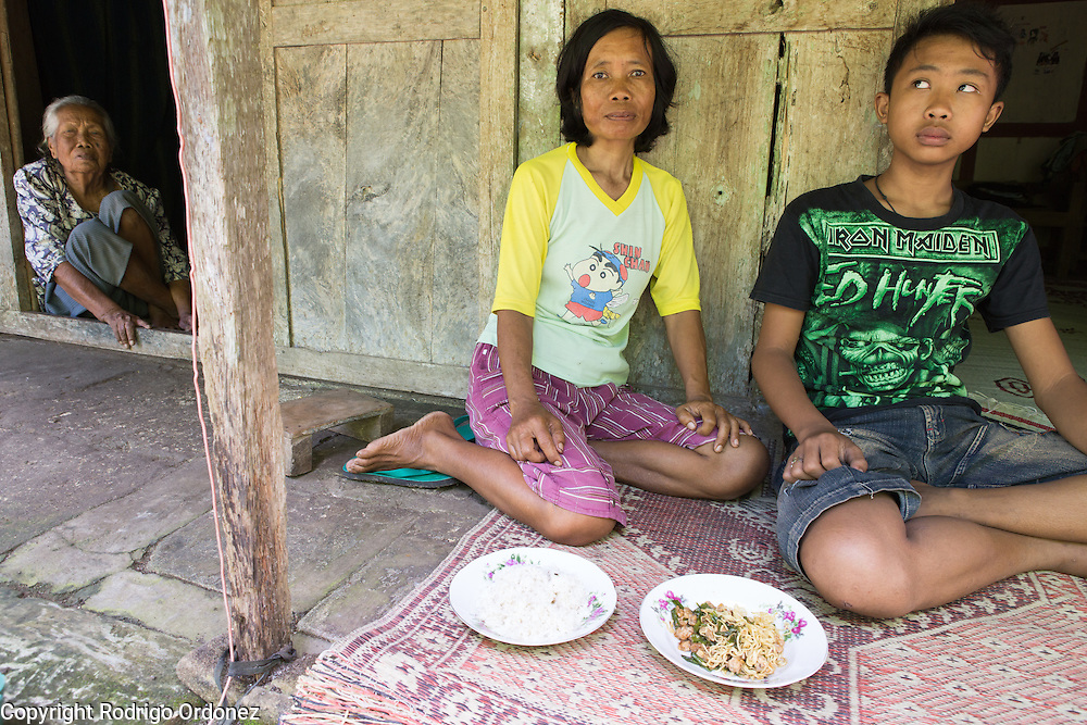 Samiyah, 45 (right), is a landless farmer who works for others as a daily laborer; she is not a member of the female farmers organization led by Suparjiyem. Sitting by the front door of her house, she shows the daily meal she will share with her son Reno, 12 (right): a plate of rice and a plate of noodles. In the image (left) is also her mother Wati, around 80 years of age. They live in the village of Wareng, Wonosari subdistrict, Gunung Kidul district, Yogyakarta Special Region, Indonesia.