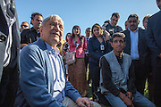 George Soros, chairman and founder of the Open Society Foundations, talking to Gheorghe Mircea (right) a local inhabitant, at the Roma part of Frumusani.
