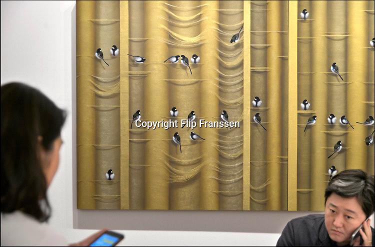 Nederland, Maastricht, 16-3-2016 Tefaf, The European Fine Art Fair in het MECC. Dit is de grootste kunstbeurs in Europa en ter wereld. 29e editie. Onder de topstukken bevindt zich een vroeg werk van Rembrandt van Rijn, uit de serie zintuigen is het de Reuk, geur.Een van de duurste objecten is een manuscript van de Gebroeders Van Limburg uit circa 1407, met dertig tekeningen. Op de foto medewerkers van een galerie uit Seoul voor een schilderij met vogeltjes.Foto: Flip Franssen