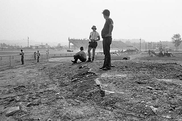 Spectators stand atop remains of old Watkins Glen course after initial stage of reconstruction, July 1971. Old pit lane visible in background.