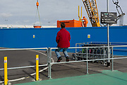 A bystander watches the industrial project, a construction crane and workman appearing over airport baggage trolleys and blue hoarding at City Airport, on 10th October 2019, east London, England.