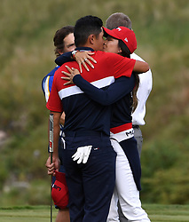 Team USA's Collin Morikawa (left) hugs wife Katherine Zhu after securing enough points to win the Ryder Cup for Team USA on the 18th hole during day three of the 43rd Ryder Cup at Whistling Straits, Wisconsin. Picture date: Sunday September 26, 2021.