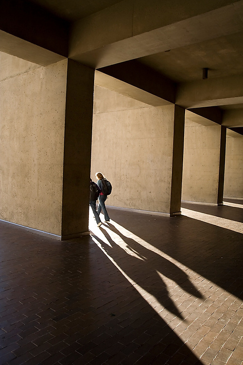 Students cast long shadows as they pass outside Kane Hall on the University of Washington campus in Seattle, Washington on October 12, 2006.