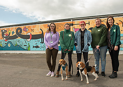 Edinburgh Dog and Cat Home 'unveiled' a colourful 80-foot mural along the Seafield Promenade this morning. The large-scale artwork occupies a wall previously covered in graffiti along the Seafield shoreline. Designed and painted by local artists, Studio N_Name, the mural will embodies the colourful people, heritage and environment of the local community. This project was made possible through a partnership with Edinburgh Shoreline Project, which chose to support the mural as part of their mission to celebrate the city's 27km of coastline. Pictured: Charlotte Johnson, Edinburgh Shoreline project manager, Katie Guthrie, one of the artists from Studio N_Name, Alanna Brady, Special Gifts Fundraiser at Edinburgh Dog and Cat Home with Dog and Cat Home staff, and dogs<br /> © Jon Davey/ EEm