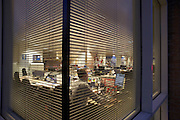 Seen through a window as daylight fades, an employee works late at the United Biscuits Group offices, Hayes London