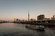 Tokyo Skytree at dusk above the Sumida River with a pleaure boat sailing past Asakusa buildings. Tokyo, Japan. Friday, January 10th 2014