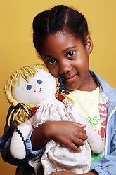 Portrait of young girl holding rag doll,