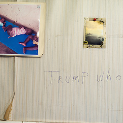 "August 4, 2017 - Tangier Island, VA - <br /> Inside the ""Situation Room,""  (named after a small briefing room in the White House) is a small room inside the former Tangier Island health clinic, where watermen gather at the end of the day to ""solve all the world's problems,"" according to Tangier Island Mayor James ""Ooker"" Eskridge (center).  Next to a picture of some orphans are scribbled the words ""Trump Who,"" which references a conversation one of the island's few democrats said about GOP Presidential candidate Donald J. Trump, ""After the election, everyone will ask Trump who?"" the person asserted, believing that Trump would lose the election.<br />   Photo by Susana Raab/Institute"