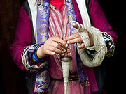 A Brokpa woman spins sheep wool using a drop spindle called a Yoekpa, Merak, Eastern Bhutan. The Brokpa, the semi-nomads of the villages of Merak and Sakteng are said to have migrated to Bhutan a few centuries ago from the Tshona region of Southern Tibet. Thriving on rearing yaks and sheep, the Brokpas have maintained many of their unique traditions and customs.