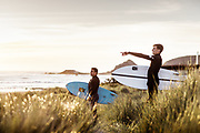 Surfers standing in the grass on the sand dunes at L'Etacq, St Ouen's Bay, Jersey, watching the surf and waves at sunset.
