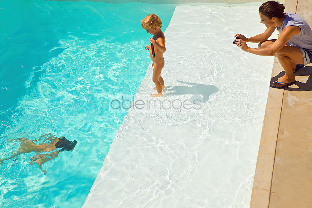 Woman Taking Photo of Children in Swimming Pool