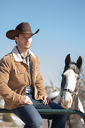 cowboy sitting on a fence with a horse nearby