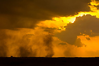 Smoke in the sky from a controlled burn at sunset, Masai Mara National Reserve, Kenya