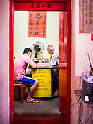 """09 AUGUST 2014 - BANGKOK, THAILAND: Men in the office of the Ruby Goddess Shrine in the Dusit section of Bangkok before a Ghost Month community meal. The seventh month of the Chinese Lunar calendar is called """"Ghost Month"""" during which ghosts and spirits, including those of the deceased ancestors, come out from the lower realm. It is common for Chinese people to make merit during the month by burning """"hell money"""" and presenting food to the ghosts. At Chinese temples in Thailand, it is also customary to give food to the poorer people in the community.        PHOTO BY JACK KURTZ"""